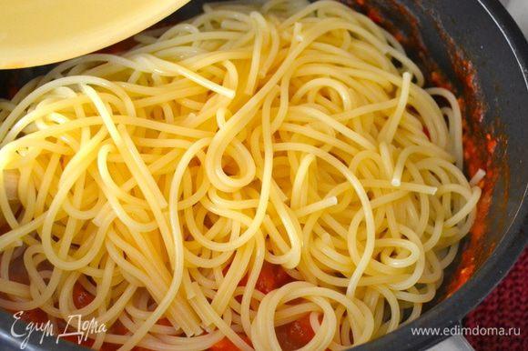 Спагетти отварить в большом количестве соленой воды, согласно указаниям на упаковке. Готовые спагетти слить и выложить в сковороду с помидорным соусом. Как следует перемешать и снять с огня.