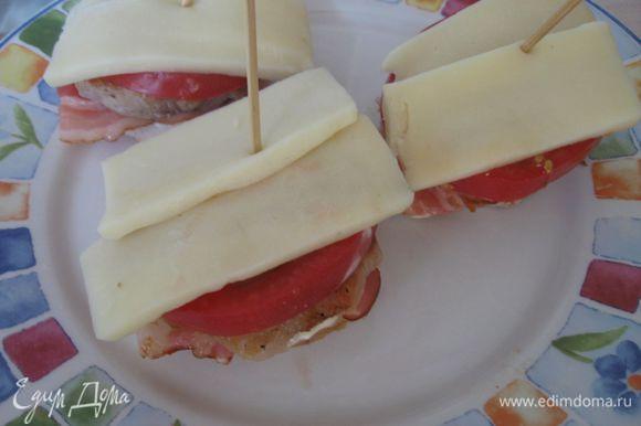 На помидор выложить тонкие кусочки сыра. Скрепить «пирамидку» деревянной шпажкой. Форму застелить пергаментной бумагой. Духовку разогреть до 200 градусов. Запечь в духовке до появления румяной корочки у сыра.