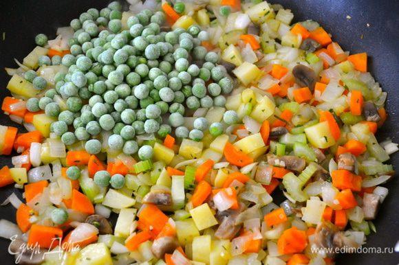Добавить замороженный зеленый горошек и продолжать еще пару минут обжаривать.