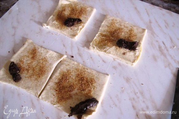 Нарежьте тесто на квадратики, посыпьте смесью корицы и сахара, и положите на уголок ложечку пасты.
