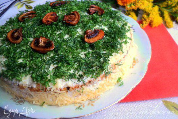 Также переслоить все пласты бисквита. Верх и бока смазать сырным кремом. Бока обсыпать тертым сыром, верх – мелко нарезанной зеленью (укроп, петрушка). Украсить поджаренными пластинками грибов. Поставить в холодильник охлаждаться на 1-2 часа.