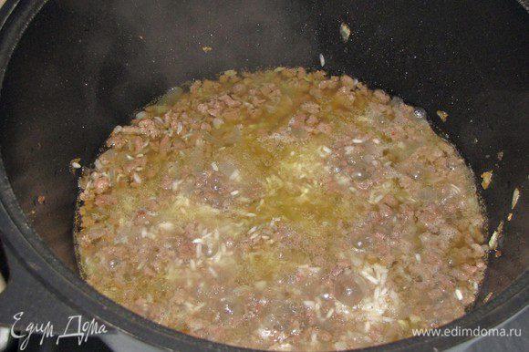 Всыпать рис, влить бульон, посолить, поперчить, добавить орегано и готовить 12 минут.