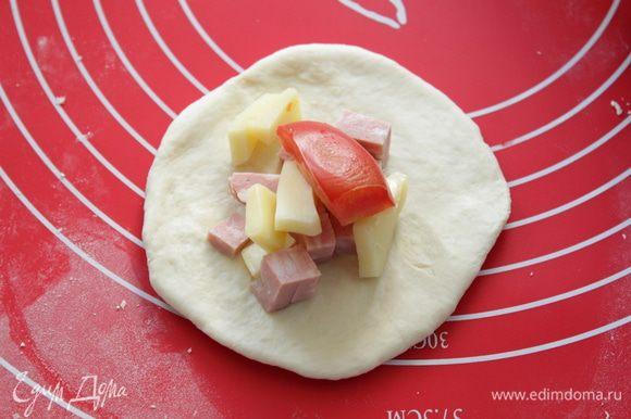 Подошедшее тесто вымесить, разделить на 12-14 частей, сделать шарик и раскатать. На него выложить начинку.