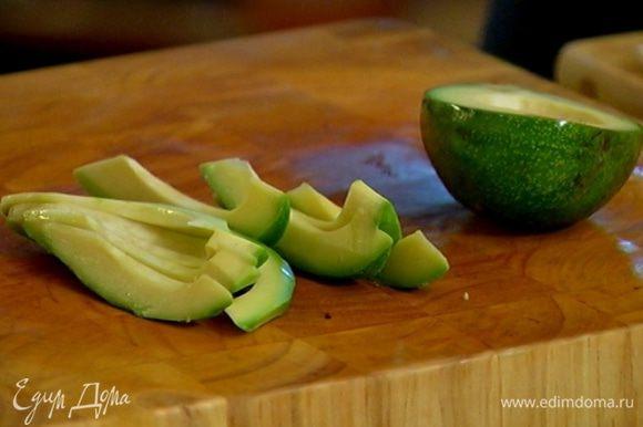 Авокадо очистить от кожуры, разрезать пополам и удалить косточку. Нарезать мякоть тонкими полосками.
