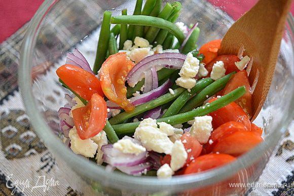 Слить воду , встряхнуть лишние капли, выложить в общее блюдо, добавить сыр Фета крошкой, помидоры на половинки, 1/4 часть порезанный лук.