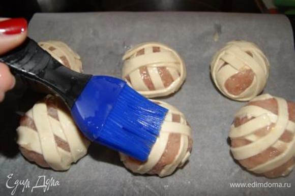 Выложить клубочки на противень, застленный бумалой для выпечки, смазанной растительным маслом. Клубочки смазать взбитым яйцом.