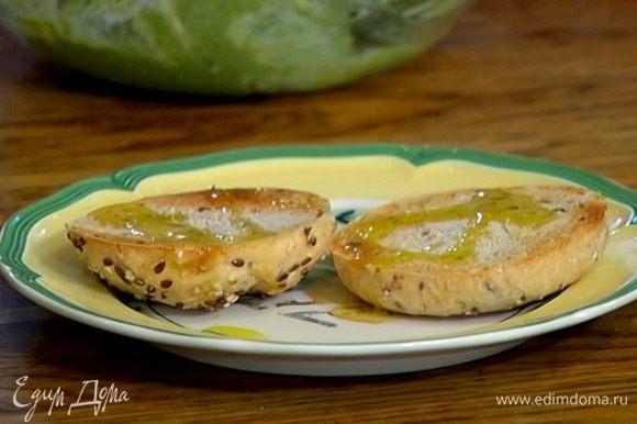 Булки разрезать пополам вдоль, подсушить в тостере и сбрызнуть оставшимся оливковым маслом.