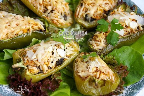 Готовые перцы выкладываем на листья салата. Сверху слегка сбрызгиваем оливковым маслом, присыпаем миндальными лепестками и тёртым сыром. Украшаем петрушкой.