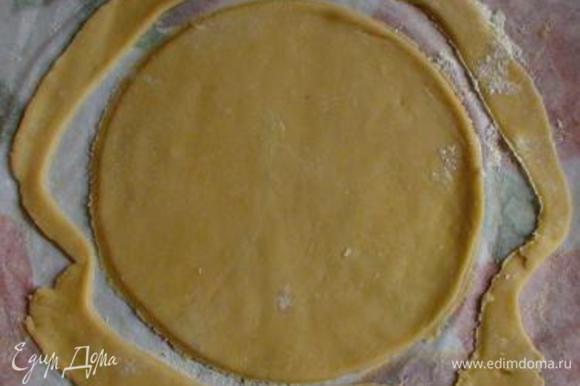 Выложить 1 часть теста на присыпанный мукой пергамент и раскатать (при необходимости можно посыпать мукой). Обрезать корж по дну формы или крышке диаметром 20 см (можно просто надавить крышкой контур круга, а обрезать уже испеченный корж - как удобнее). Обрезки оставить на пергаменте (они понадобятся для оформления боков торта) и все вместе прямо на бумаге перенести на противень.