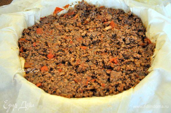 Каждый лист фило смазать оливковым маслом и уложить друг на друга в форму диаметром 24 см. Тесто должно сильно свисать по краям. На тесто выложить мясную начинку,
