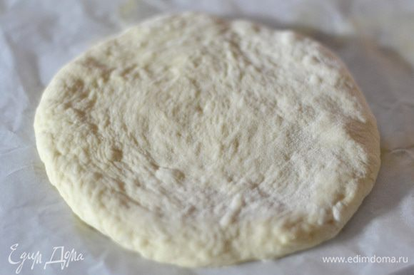 Поднявшееся тесто разделить на 4 части,выложить на пергамент, слегка присыпанный мукой и сформировать руками лепешки. Накрыть полотенцем и оставить на 10 минут.
