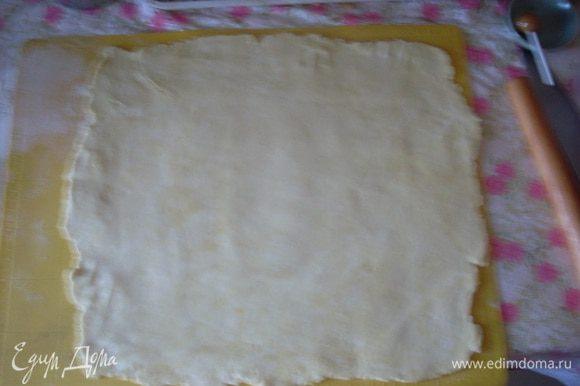 Делю тесто на 2 части (одна побольше - для нижнего пласта). Раскатываю нижний пласт размером 40х35 см (я предпочитаю раскатывать на силиконовом коврике - так удобнее переносить пласты на противень). Противень не смазываю - тесто довольно жирное. Нижний пласт укладываю на противень.