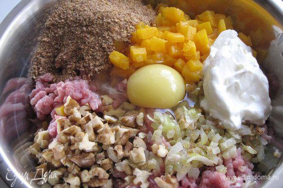 К мясному фаршу добавьте жареный лук с чесноком, тыкву, орехи, панировочные сухари, сметану, яйцо. Посолите и поперчите. Хорошо перемешайте.