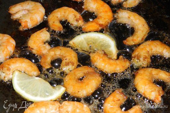 Очищенные креветки обжарить на растительном масле с дольками лимона.