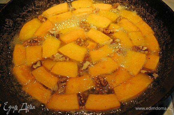 Когда карамель немного потемнеет в нее уложим тыкву и в промежутки кусочки орехов. Сковороду прикроем фольгой и поместим в разогретую до 200 градусов духовку на 15 минут. Вынуть сковороду с тыквой из духовки, дать немного остыть.