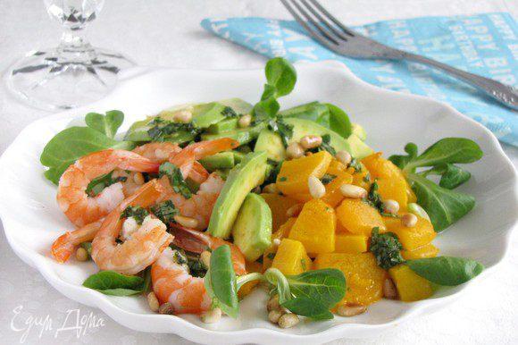 На салат выложите кучками тыкву, авокадо, креветки. Полейте заправкой, посыпьте кедровыми орешками.