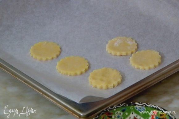 Противень выстелить бумагой для выпечки, выложить сырные кружки и отправить в разогретую духовку на 10 минут.
