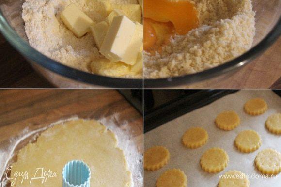 Для приготовления теста смешать муку, соль, оба вида сахара и разрыхлитель. Добавить нарезанное на кубики масло и порубить всё в крошку. Добавить желток и, если есть необходимость, можно добавить 1 ст.л. ледяной воды, и быстро собрать тесто в шар. Завернуть его в плёнку и убрать в холодильник минимум на полчаса. Далее раскатать тесто на присыпанной мукой поверхности в пласт толщиной 3 мм. Выемкой для печений или стаканом вырезать маленькие круги, диаметром 4-5 см. Переложить их на противень, застеленный пергаментом, и выпекать в разогретой до 180-200*С духовке 10-12 минут.