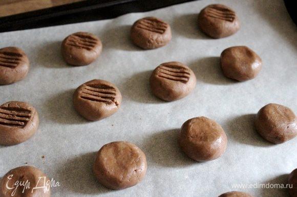 Выложить шарики теста на застеленный пергаментом противень. Тыльную сторону зубчиков вилки чуть-чуть смазать растительным маслом, затем опустить в отложенное какао и придавить зубцами печенье. Выпекать 15-20 минут при 180*С. Готовое печенье остудить.