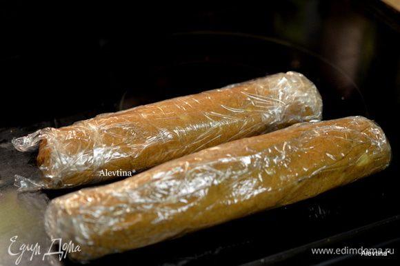 Выкладываем тесто, поделив на 2 части на пищевую пленку. Выравниваем и закругляем, катая в пленке по столу.