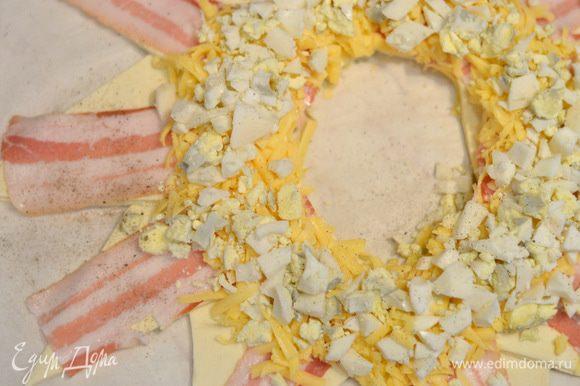 Затем поверх сыра выложить отварные и мелко порубленные яйца, засыпать остальным сыром.