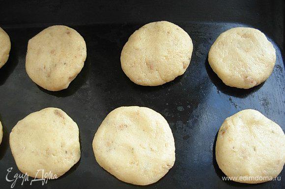 От теста отщипывать кусочки, размером с грецкий орех, катать шарик, а затем приплюснуть, придав форму круглой печеньки. Выложить на не смазанный лист, либо на пергамент, на довольно большом расстоянии, печенье немного приподнимается.