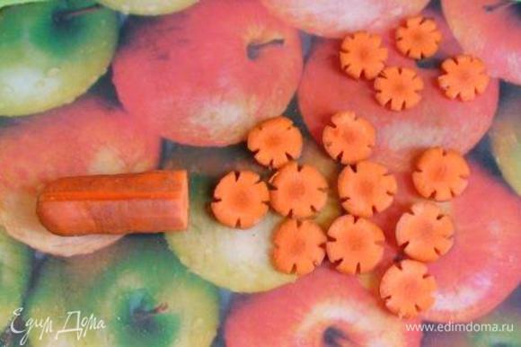 Морковь помыть, почистить, сделать на ней 5-6 продольных разрезов. Порезать морковь на кружочки - получатся цветочки.