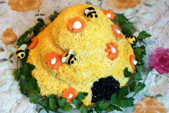 """Смешать оставшийся желток с каплей майонеза и сформировать из него и порезанных на кружочки оливок пчел. Глазки сделать из черного перца горошком, крылья - из лепестков миндаля. Украсить салат цветочками из моркови, посадить на него """"пчел"""", сделать для них дверцу из измельченных на терке оливок. Выложить вокруг салата зелень."""
