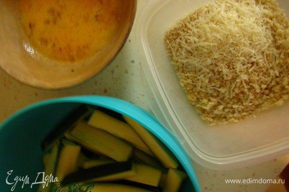 Панировочные сухари смешать с тертым пармезаном. Каждый кусочек цукини поместить в яйцо, затем в сухари.