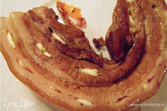 Чеснок нарежьте лепестками, но не очень тонко, что бы он чувствовался в последствии в нашем блюде. Острым ножом делайте надрезы и нашпигуйте грудинку чесноком.
