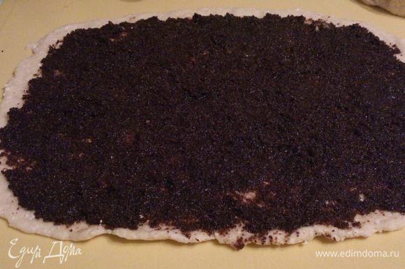 Тесто разрезат на 2 части.Раскатать каждую в пласт, толщиной 0,5 см. нанести маковую начинку тонким слоем