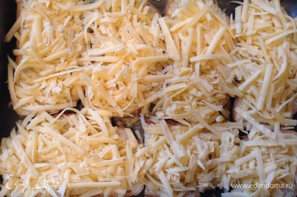 Вынуть из духовки протвень и уложить на бутерброды первым слоем сыр, затем раздавленный чеснок.