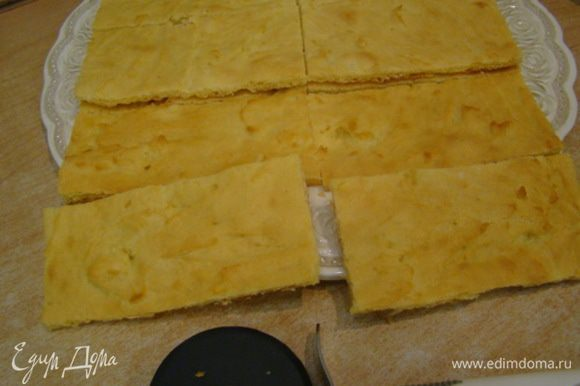 Подравнять края, положить один корж на другой, разрезать ножом для пиццы на 8 прямоугольников.