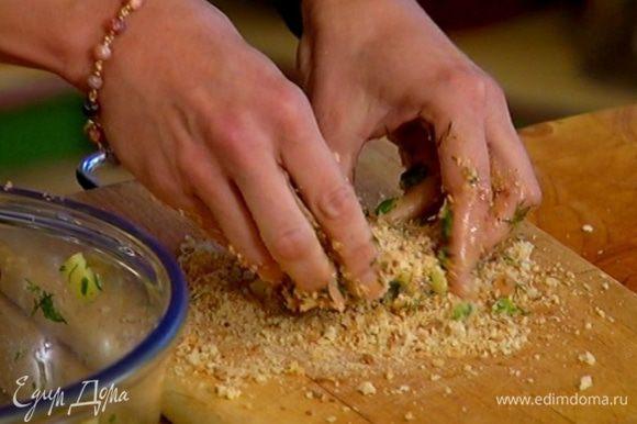 На рабочую поверхность насыпать хлебную панировку, сформировать из фарша биточки и обвалять их со всех сторон в сухарях.