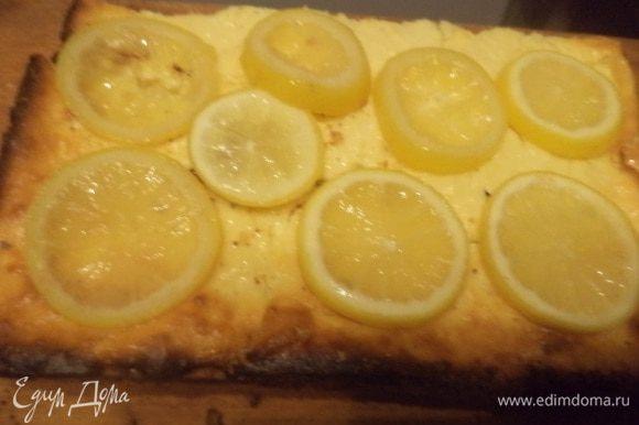 Лимон тщательно вымыть, нарезать тонкими кружками, выложить в маленькую кастрюльку, засыпать сахаром, влить воду и проварить на маленьком огне около 10 минут. Выложить кусочки лимона на испечённый чизкейк. Очень вкусно!!!