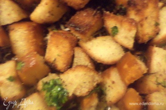 На сковороду, где жарились бекон и колбаса, добавить ещё 2 ст. л. растительного масла и выложить кусочки хлеба, подрумянить хлеб. Добавить рубленую петрушку и обжарить .