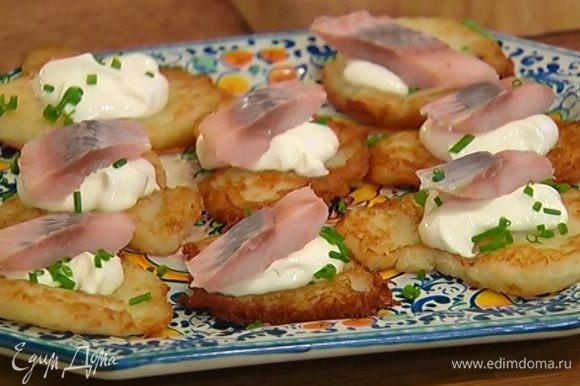 Горячие драники выложить на тарелку, намазать сметаной, посыпать шнитт-луком, сверху разложить кусочки сельди.
