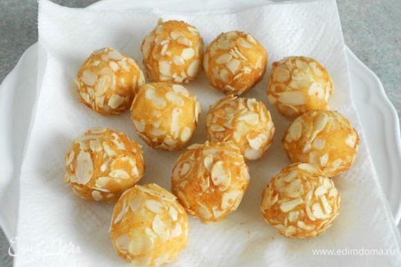 1 л масла хорошо нагрейте во фритюрнице или в высоком сотейнике и обжарьте картофельные шарики порциями примерно по 2 мин. Выкладывайте их на блюдо с бумажными салфетками.