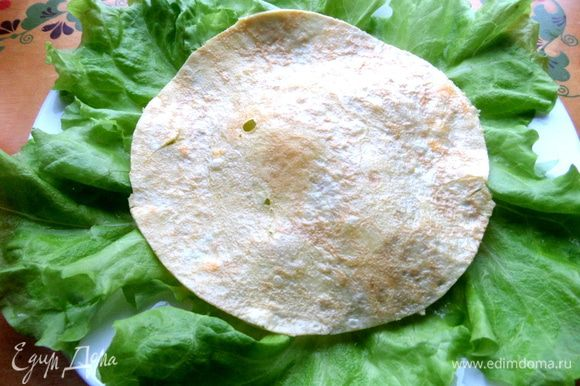 Тонкий омлетик обрезаем и кладём как основу салата.
