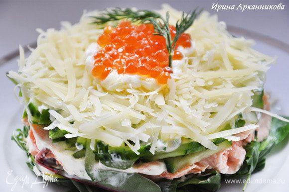 На тарелку поставить кондитерское кольцо и выложить в него слоями: салатную смесь, семгу кусочками, огурец, сыр. Каждый слой смазать заливкой. Украсить икрой и укропом. Снять кольцо.
