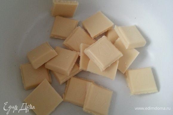Белый шоколад разламываем на кусочки и, добавив часть сливок, растапливаем на водяной бане.
