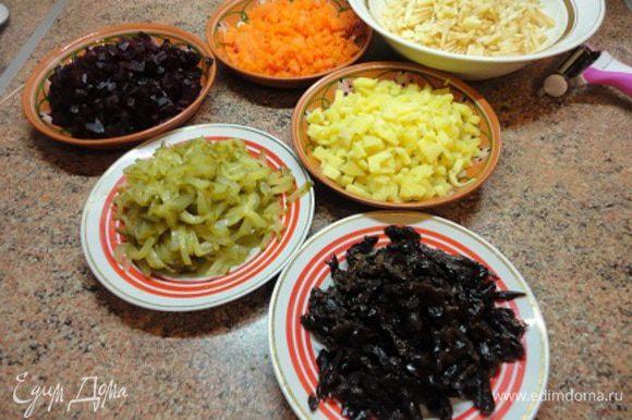Все овощи можно натереть на крупной терке, но я предпочитаю нарезать ножом: картофель, морковь и свеклу – кубиками. Яблоки очистить и нарезать соломкой. Огурцы тоже нарезать соломкой и дать стечь рассолу. Чернослив нарезать соломкой.