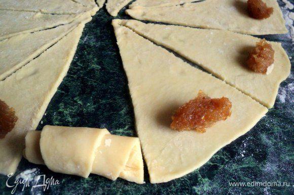 Положить на каждый треугольник 1 чайную ложку начинки и скатать в рулетик. У меня начинка – густое розовое варенье и варенье из айвы. Для начинки также можно использовать измельченные орехи, изюм, вишни.