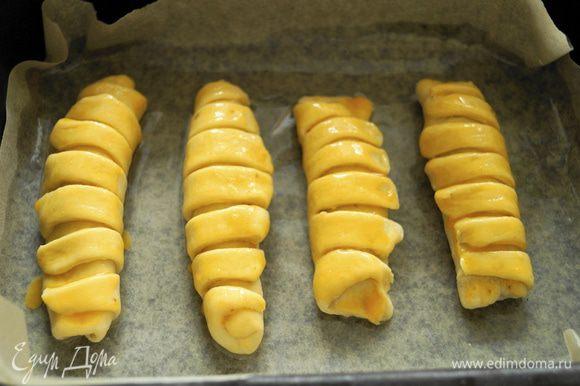 Выложить булочки на противень застеленный пергаментом и смазанный маслом, смазать булочки взбитым желтком.
