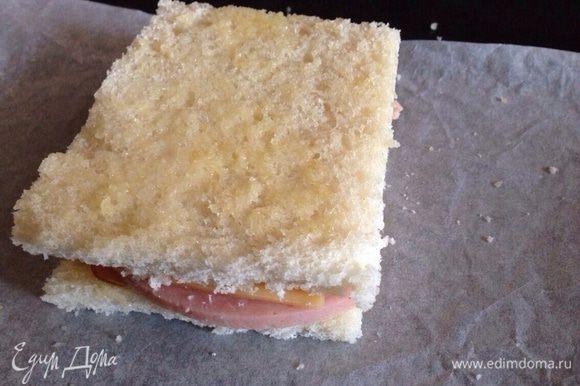 Накрыть оставшимся ломтиком хлеба, смазать сливочным маслом. И отправить запекаться в духовку на 5 минут, при температуре 180 градусов. Затем перевернуть и поставить еще на 5 минут в духовку.