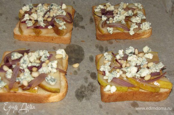 Посыпьте раскрошенным сыром и кедровыми орешками. Снова поставьте тосты под гриль и готовьте, пока сыр не начнет плавиться, 2-3 минуты.