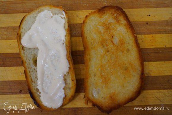 Приступаем к завершающему этапу приготовления бутерброда. Наносим майонез на гренку со стороны не намазанной чесноком.