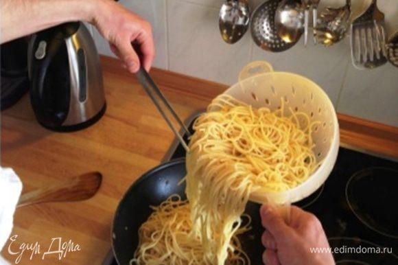 Спагетти выкладываем на сковороду и помешиваем на малом огне.