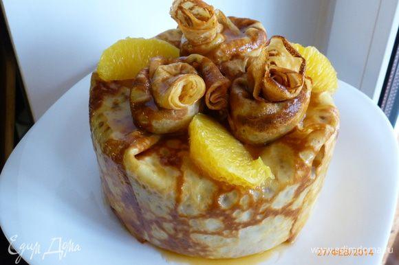 Пирог со всех сторон кисточкой обмазываем абрикосовым сиропом. Оставшиеся три блина сворачиваем трубочкой, складываем по спирали, формируя цветок. Для фиксации цветы можно закрепить зубочисткой. Блинчатые цветы так же обмазываем сиропом. Украшаем пирог дольками апельсина и цедрой. Приятного аппетита!