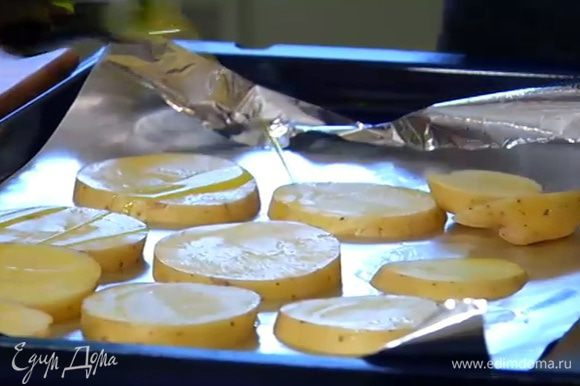 Противень выстелить фольгой, выложить картофель, сбрызнуть 1–2 ст. ложками оливкового масла и отправить под гриль на 10 минут.